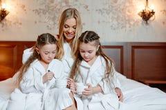 Den lyckliga familjen, modern och döttrarna kopplar samman, sitter och kopplar av på a Arkivfoton