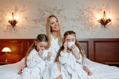 Den lyckliga familjen, modern och döttrarna kopplar samman, sitter och kopplar av på a Royaltyfria Bilder