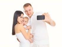 Den lyckliga familjen, modern och fadern med behandla som ett barn gör självståenden på smartphonen Arkivfoton