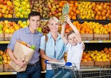 Den lyckliga familjen mot hyllor av frukter har shopping Royaltyfri Foto