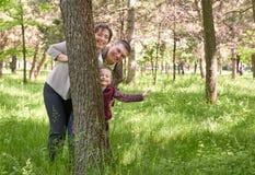 Den lyckliga familjen och barnet i sommar parkerar Folk som döljer och spelar bak ett träd Härligt landskap med träd och grönt gr Royaltyfri Fotografi