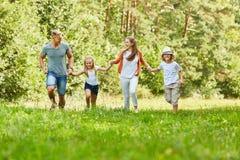 Den lyckliga familjen och ungar kör i parkera Fotografering för Bildbyråer