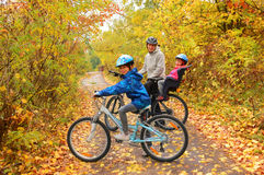 Den lyckliga familjen på cyklar i höst parkerar Fotografering för Bildbyråer