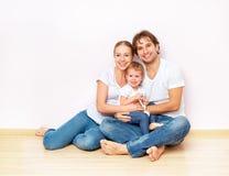 Den lyckliga familjen på golv nära den tomma väggen i lägenheten som köps på, intecknar Royaltyfri Fotografi