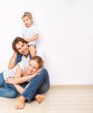 Den lyckliga familjen på golv nära den tomma väggen i lägenheten som köps på, intecknar Arkivfoto