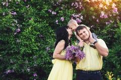 Den lyckliga familjen parkerar in med den blommande lilan Den lyckliga mamman, farsan och sonen går på solnedgången Begrepp av de Royaltyfri Fotografi