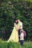 Den lyckliga familjen parkerar in med den blommande lilan Den lyckliga mamman, farsan och sonen går på solnedgången Begrepp av de Arkivbilder