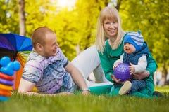 Den lyckliga familjen plaing i parkera Arkivbilder