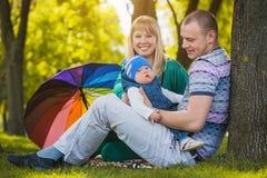Den lyckliga familjen plaing i parkera Royaltyfri Foto