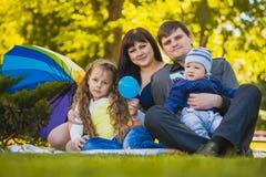 Den lyckliga familjen plaing i parkera Arkivbild