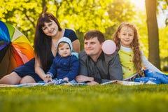 Den lyckliga familjen plaing i parkera Arkivfoton