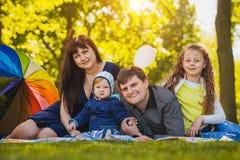 Den lyckliga familjen plaing i parkera Fotografering för Bildbyråer