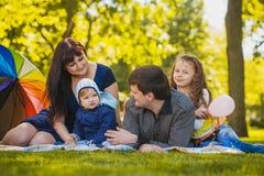 Den lyckliga familjen plaing i parkera Arkivfoto