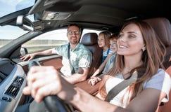den lyckliga familjen reser i en bekväm bil arkivfoto
