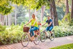 Den lyckliga familjen rider cyklar utomhus arkivfoto