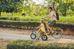 Den lyckliga familjen rider cyklar utomhus och att le Avla på en cykel och en son på en balancebike arkivbild
