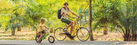 Den lyckliga familjen rider cyklar utomhus och att le Avla på en cykel och en son på ett balancebikeBANER, långt format royaltyfria bilder