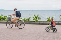 Den lyckliga familjen rider cyklar utomhus och att le Fader på ett b arkivbilder