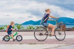 Den lyckliga familjen rider cyklar utomhus och att le Mamma på en cykel royaltyfria foton