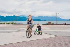 Den lyckliga familjen rider cyklar utomhus och att le Mamma på en cykel royaltyfria bilder