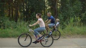 Den lyckliga familjen rider på cyklar i skogen arkivbild