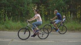 Den lyckliga familjen rider på cyklar i skogen arkivfilmer