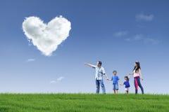 Den lyckliga familjen ser hjärtamoln i parkera Arkivfoton