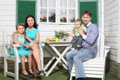 Den lyckliga familjen sitter på den vita trätabellen Royaltyfri Foto