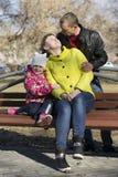 Den lyckliga familjen sitter på en bänk i parkera Royaltyfria Bilder