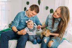 Den lyckliga familjen sitter på sängen och spelar med det babby closen colors slappt övre siktsvatten för liljan royaltyfri fotografi