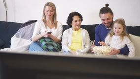 Den lyckliga familjen sitter på soffan och hållande ögonen på tv med popcorn tillsammans stock video