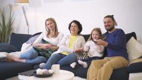 Den lyckliga familjen sitter på soffan tillsammans och hållande ögonen på bra kvalitet för komedifilm på tv stock video