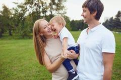 Den lyckliga familjen skrattar i parkerar royaltyfri bild