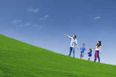 Den lyckliga familjen snubblar på kullen Arkivfoto