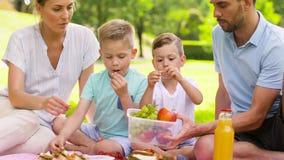 Den lyckliga familjen som äter frukter på picknick på, parkerar arkivfilmer
