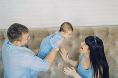 Den lyckliga familjen som består av mamma- och farsa` s, behandla som ett barn pojken Arkivfoton