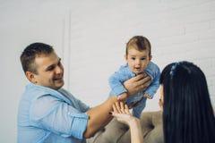 Den lyckliga familjen som består av mamma- och farsa` s, behandla som ett barn pojken lyckliga förhållanden för familj Arkivbilder