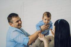 Den lyckliga familjen som består av mamma- och farsa` s, behandla som ett barn pojken lyckliga förhållanden för familj Royaltyfria Bilder