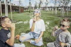 Den lyckliga familjen som blåser bubblor i, parkerar utomhus och har gyckel arkivfoton