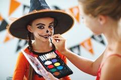 Den lyckliga familjen som får klar för halloween, gör smink arkivfoton