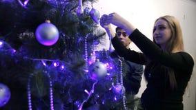 Den lyckliga familjen som förväntar barnet, behandla som ett barn och att dekorera julträdet arkivfilmer