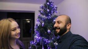 Den lyckliga familjen som förväntar barnet, behandla som ett barn och att dekorera julträdet stock video