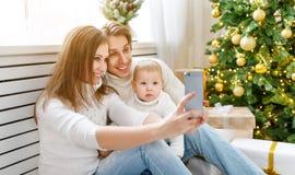 Den lyckliga familjen som fotograferas på telefonen, gör selfies i jul M Royaltyfria Bilder