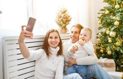 Den lyckliga familjen som fotograferas på telefonen, gör selfies i jul M Royaltyfri Bild