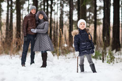 Den lyckliga familjen som går i en vinter, parkerar Fotografering för Bildbyråer