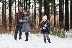 Den lyckliga familjen som går i en vinter, parkerar Arkivfoto