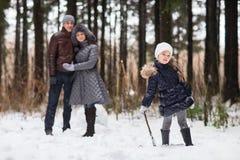 Den lyckliga familjen som går i en vinter, parkerar Royaltyfria Foton