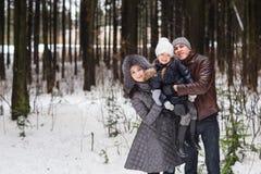 Den lyckliga familjen som går i en vinter, parkerar Royaltyfria Bilder