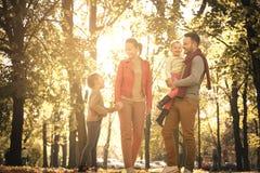 Den lyckliga familjen som går den offentliga ho, parkerar Fotografering för Bildbyråer