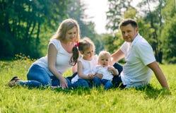 Den lyckliga familjen som gitting på gräs parkerar in royaltyfria foton
